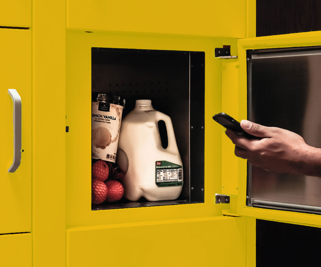 Grabbing food from a yellow smart locker with it's door open.